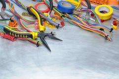 Elektriska hjälpmedel och del- satsen som ska användas i elektriska installationer på grå färger, belägger med metall bakgrund Royaltyfria Bilder