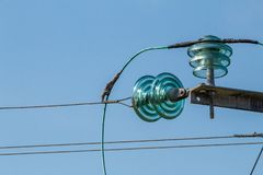 Elektriska isolatorer och trådar för turkos på en blå himmel arkivbilder