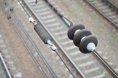 Elektriska isolatorer på kontakten binder på bakgrunden av en suddig järnvägsspår Makrofoto med selektiv focu arkivbilder