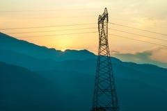 Elektriska kraftledningar på solnedgången Arkivfoto