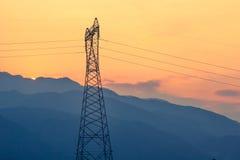 Elektriska kraftledningar på solnedgången Arkivfoton