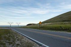 Elektriska linjer för makt från den elektriska växten för Hydro vid vatten och vägen med tecknet royaltyfri foto