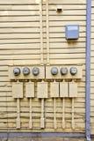 Elektriska meter på sida av det gamla huset Royaltyfri Foto