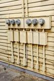 Elektriska meter på sidan av det gamla huset som konverteras till lägenheter Royaltyfri Bild