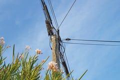 Elektriska poler av hög spänning i det vita molnet och blå himmel Royaltyfri Bild