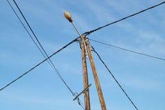 Elektriska poler av hög spänning i det vita molnet och blå himmel Arkivbild