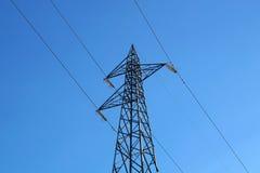 Elektriska poler av hög spänning i det vita molnet och blå himmel Arkivfoton