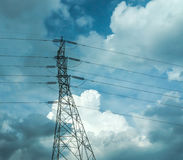Elektriska poler av hög spänning i det vita molnet och blå himmel/elektriska polkraftledningar och trådar med eq för blå himmel/h Royaltyfri Foto