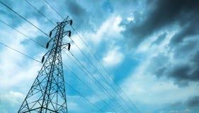 Elektriska poler av hög spänning i det vita molnet och blå himmel/elektriska polkraftledningar och trådar med eq för blå himmel/h Royaltyfri Bild