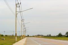 Elektriska poler bredvid gatan Arkivfoton