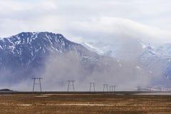elektriska poler för hög spänning som lokaliseras i bygden med snö Arkivfoto