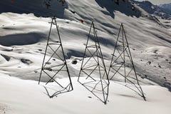 Elektriska poler i den fantastiska snön täckte landskap och berg i fjällängarna Schweiz Royaltyfri Foto