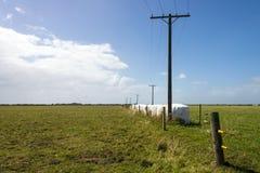 Elektriska poler och trådar med foder av höbaler Royaltyfria Foton