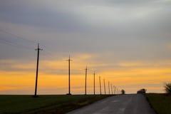 Elektriska poler på en landsväg och härliga moln på solnedgången Royaltyfri Fotografi
