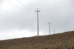 Elektriska poler på jordningen under ett molnigt Royaltyfria Foton