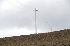 Elektriska poler på jordningen under ett molnigt Royaltyfri Fotografi