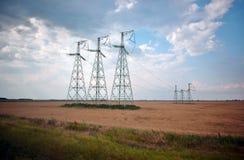 Elektriska poler stiger ovanför fältet med vete Arkivbilder