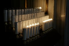 Elektriska stearinljus med glödande lampor i basilika Arkivbilder
