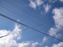 Elektriska trådar i snön mot bakgrunden av moln och blå himmel fotografering för bildbyråer