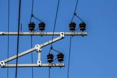 Elektriska trådar med isolatorer sträcks ut överst på en himmel royaltyfri foto