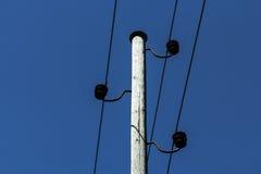 Elektriska trådar med isolatorer sträcks ut överst på en himmel royaltyfria bilder
