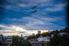 Elektriska trådar med solnedgång och stad i bakgrund royaltyfri fotografi