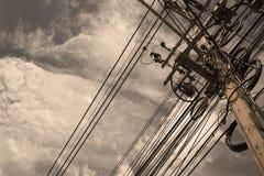 Elektriska trådar på en pol på en molnig himmel Arkivfoton