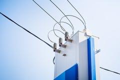 Elektriskt bräde med hög-spänning trådar mot den blåa himlen arkivbild