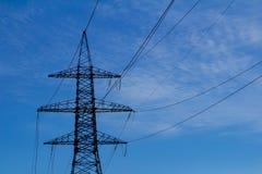 Elektriskt högt spänningstorn med den elektriska linjen mot blå himmel för moln Arkivfoto