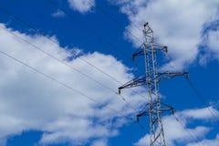Elektriskt högt spänningstorn med den elektriska linjen mot blå himmel för moln Royaltyfri Fotografi