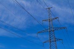 Elektriskt högt spänningstorn med den elektriska linjen mot blå himmel för moln Royaltyfri Foto