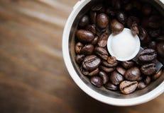 Elektriskt kaffe maler maskinen med nya kaffebönor inom Kaffekvarn på en brun trätabell i köket Royaltyfri Fotografi