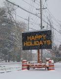 Elektriskt mobilt tecken för vägtrafik vid sidan av en dold väg för snö med att falla för snö, som säger, lyckliga ferier arkivfoton