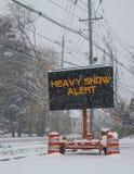 Elektriskt mobilt tecken för vägtrafik vid sidan av en dold väg för snö med fallande varning för snö av varningen för tung snö arkivbild