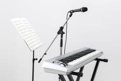 Elektriskt piano, mikrofon och musikställning Royaltyfri Foto