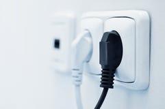 Elektriskt plug in en stickkontakt Arkivfoto