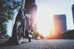Elektriskt stads- trans. Ung man som är klar att rida hans elektriska sparkcykelcykel i mitten av en stad innovativt arkivfoton