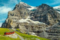 Elektriskt turist- drev med det berömda Eiger berget, Bernese Oberland, Schweiz arkivfoton