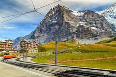 Elektriskt turist- drev och Eiger norr framsida, Bernese Oberland, Schweiz Royaltyfri Bild