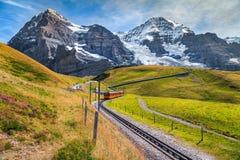 Elektriskt turist- drev och höga snöig berg med glaciärer, Schweiz arkivfoto