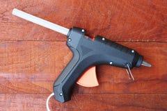 Elektriskt varmt limvapen på en wood bakgrund arkivbild