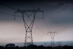 ElektrizitätsübertragungsStromleitungen am Sonnenuntergang Hochspannungsturm stockbild
