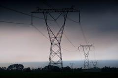 ElektrizitätsübertragungsStromleitungen am Sonnenuntergang Hochspannungsturm stockfotografie