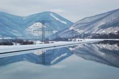 Elektrizitätspole durch Wasser Lizenzfreies Stockfoto