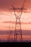 Elektrizitätszeilen mit Sonnenunterganghimmeln Stockbild