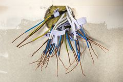 Elektro blootgestelde verbonden draden die van contactdoos op witte muur uitpuilen Elektro bedradingsinstallatie Het eindigen de  royalty-vrije stock fotografie
