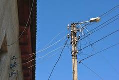 Elektro ceramische zekeringen en zwarte draden onder leidak op muur en oude lantaarn, mening van grond aan hoogste, blauwe hemel stock fotografie