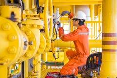 Elektro en Instrumententechnicus die en solenoïdeklep bevestigen vervangen bij zeeolie en gas ver platform stock fotografie