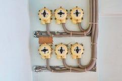 Elektro schakelt een witte pleistermuur met verbonden draden in stock fotografie