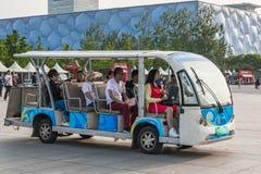 Elektroauto mit Touristen im Hintergrund des nationalen Schwimmen-Komplexes im Olympiapark von Peking lizenzfreie stockfotos